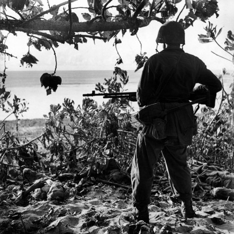 US Marine Looking at Bodies of Dead Japanese Soldiers Killed During Battle For Control of Saipan
