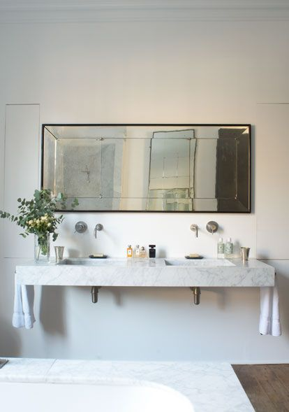 Eclectic...Vintage rectangular mirror, floating marble vanity with towel hardware on sides...Rose Uniacke