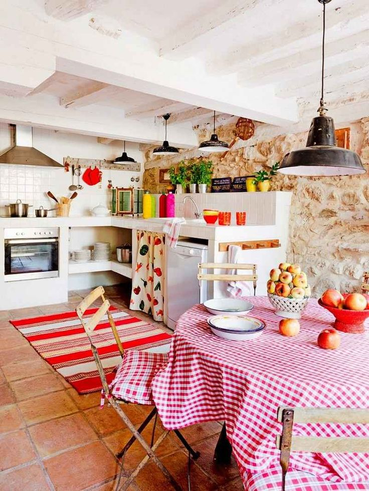 décoration maison de campagne - cuisine avec coin repas avec une déco murale en pierre naturelle,plafond blanc à la française, tapis rustique rayé en rouge et blanc et une nappe de table à motif vichy rouge et blanc