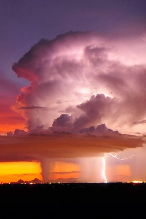 Lightning from orange clouds at sunset.