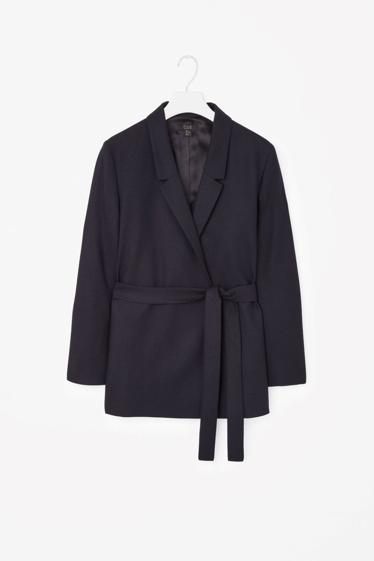 This tailored blazer is made from soft wool with a matching fabric belt, designed to tie around the waist. A slim fit, it has a crossover front, in-seam pockets and a hidden double-breasted fastening. It is completed with a smooth silky lining.