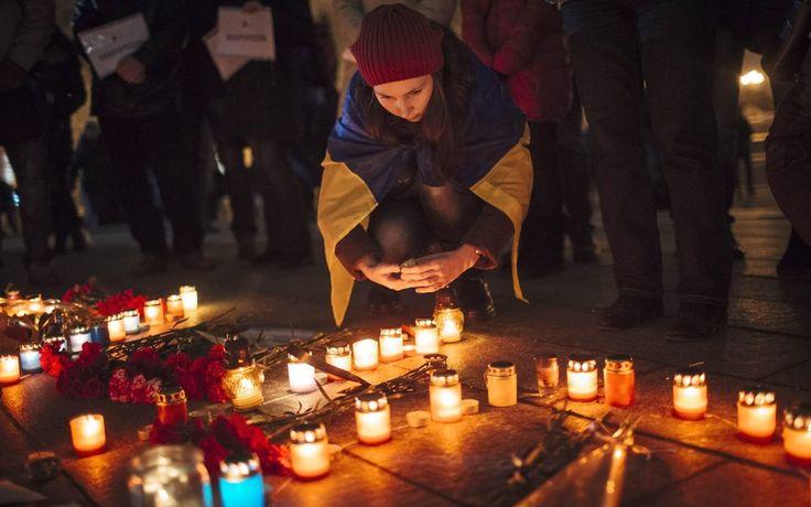 Uma garota vestida com a bandeira da Ucrânia acende uma vela em homenagem às vítimas de um bombardeio na cidade de Mariupol, leste da Ucrânia (Foto: EFE) - http://epoca.globo.com/tempo/filtro/fotos/2015/01/fotos-do-dia-24-de-janeiro-de-2015.html