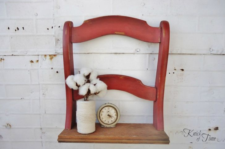 Painted red and attached to a piece of wood, this distressed chair back was given new life as a small shelf.