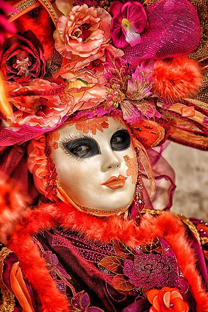 A costume of rich, saturated colors, shades of coral and pink.  Great mask with exotic kohl-outlined eyes.