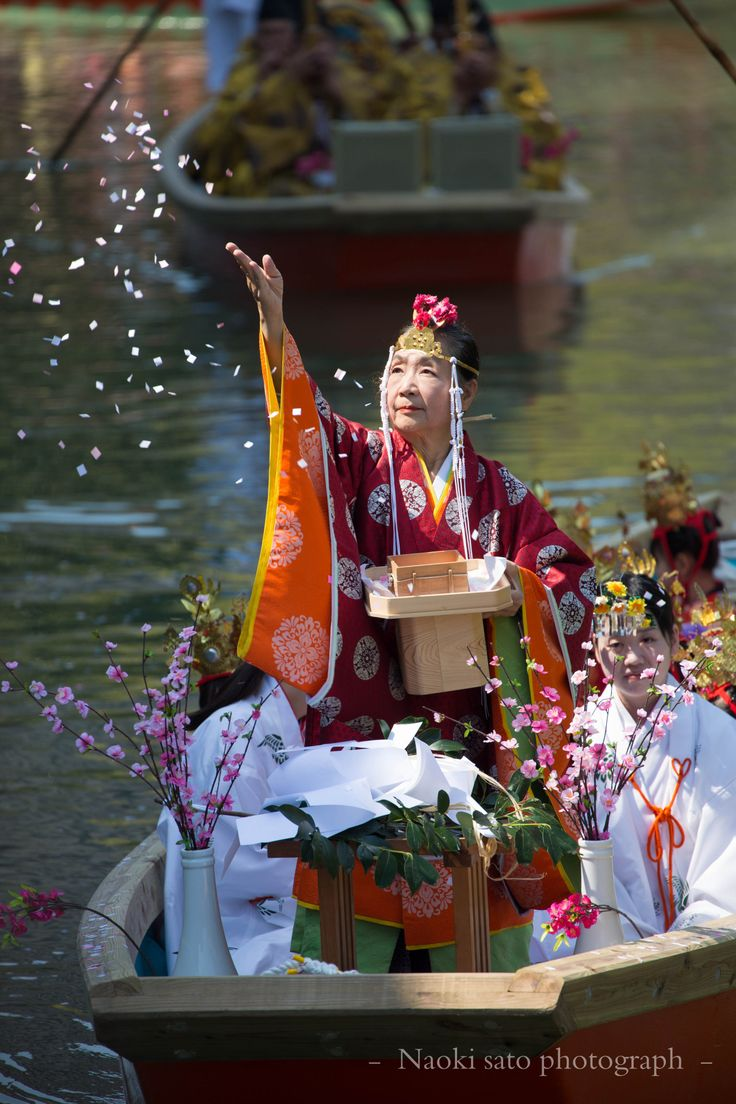 In this Shinto religious ceremony in Japan we see the ritual act of throwing flowers into the river, symbolizing freedom to the gods.