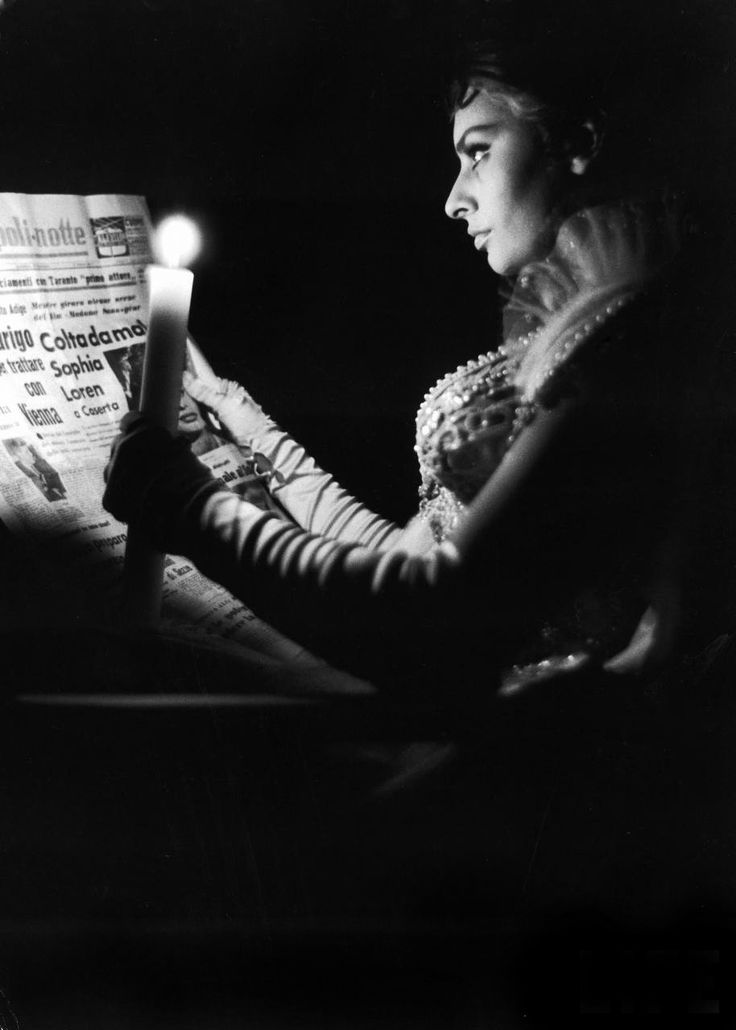 """Alfred Eisenstaedt: Actress Sophia Loren reading newspaper by candlelight while in costume for role in movie """"Madame Sans Gene"""". July 1961"""
