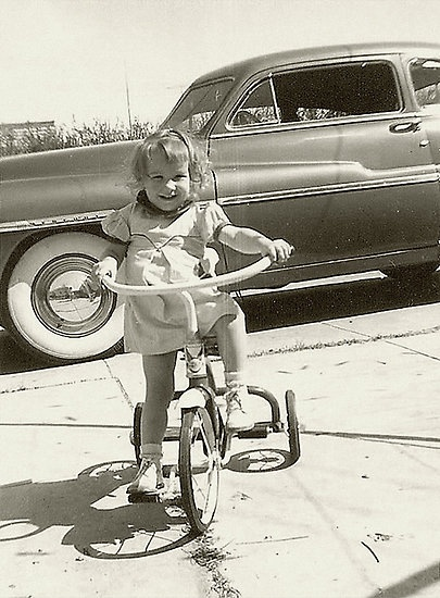 Tricycle....and white walls on the car tires-that's a Hudson Hornet. My grandfather had one....