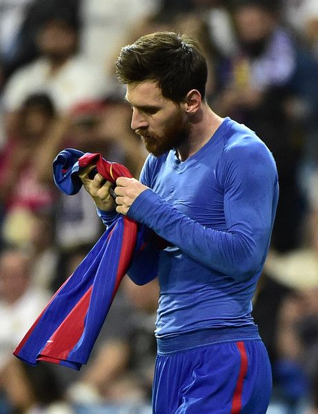 Barcelona's Argentinian forward Lionel Messi looks at his jersey after brandishing it to celebrate his goal during the Spanish league Clasico football match Real Madrid CF vs FC Barcelona at the Santiago Bernabeu stadium in Madrid on April 23, 2017..Barcelona won 3-2. / AFP PHOTO / GERARD JULIEN