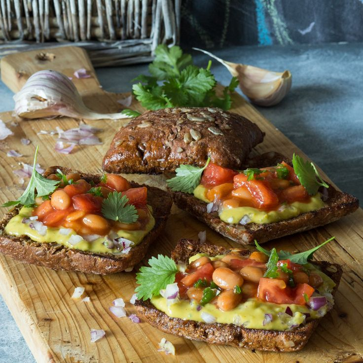Тосты с гуакамоле и белой фасолью   Ингредиенты:  Фасоль белая  в томатном соусе со специями, 0.5банки (200 г) Хлеб со злаками8кусочков Авокадо2шт. Помидоры1шт. Лук красный0.5шт. Перец чили0.5шт. Кинза4веточки Чеснок2зубчика Масло оливковое 2ст. л  Нарежьте хлеб на порционные кусочки, запеките в заранее разогретой до 200 °C духовке до легкого колера и хрустящей корочки.  Разрежьте чеснок пополам, слегка натрите каждый тост чесноком. Оставшиеся зубчики переложите в глубокую…
