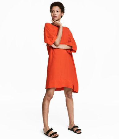 Orange. Short dress in woven, crêped fabric with a round neck and dolman sleeves. Unlined.
