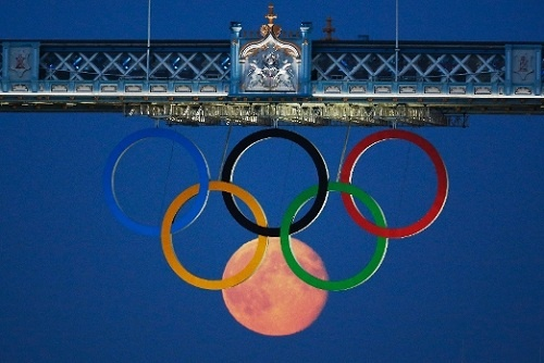 A full moon becomes the sixth Olympic ring hanging from Tower Bridge Friday night in London. Photo by Luke MacGregor/Reuters.