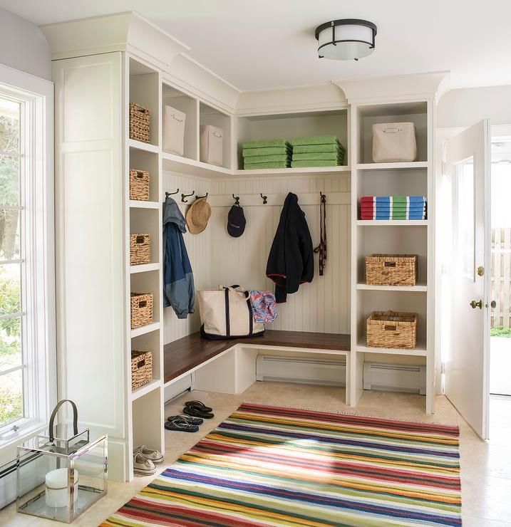 Family friendly mudroom features a L shaped built-in bench accented with beadboard trim lined with bronze hooks flanked by built-in shelving filled with woven bins.
