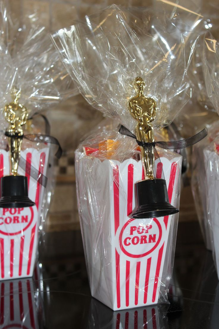 Party favors - plastic popcorn container, microwave popcorn, milk duds, candy bracelets, & an Oscar trophy