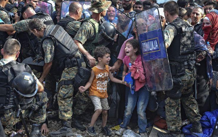 I bambini piangono mentre i migranti cercano di passare il confine bloccato dalle forze di polizia macedoni vicino alla città di Gevgelija, Macedonia