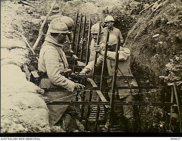 France. c. 1917. French Army soldiers in a trench in the La Harazee sector preparing an anti-personnel spiked fence. (Donor French Government)