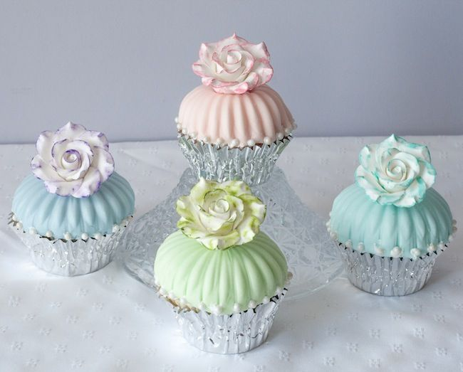 marshmallow fondant white wedding cakes surrounded with cupcakes