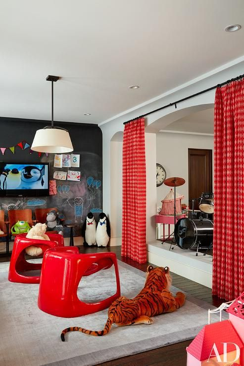 Kourtney Kardashian - Red contemporary playroom features a row of vintage chairs under a flat panel tv lining an accent wall in Benjamin Moore Chalkboard Paint.