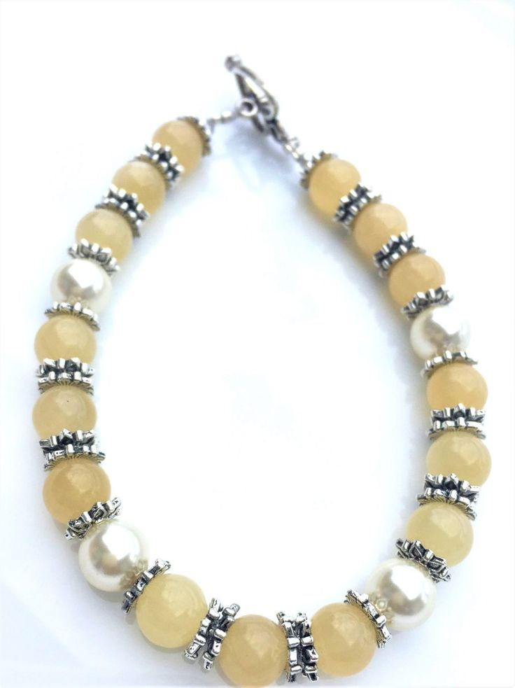 """Lemonade - Gorgeous handmade beaded bracelet, summer jewellery, vacation jewelelry, beach jewellery, outfit of the day, summer outfits of the day, handmade bracelets, handmade jewellery. 8mm Yellow Calcite Gemstone with 8mm Cream Swarovski Crystal pearls and silver-plated flower bead caps. Bracelet measures a standard 7"""" in length. All Isonia bracelets are strung by hand on a nylon and stainless-steel beading wire.  Each bracelet is unique as no two gemstones are the same size, colour or…"""