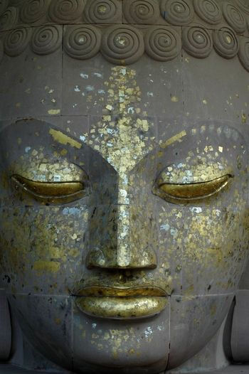 Sarnath, India. Close up that shows offering of gold leaf on the Buddha's face.