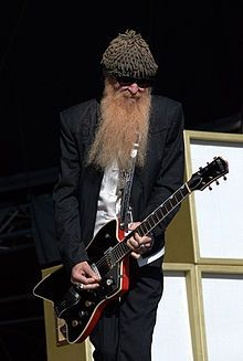 "William Frederick ""Billy"" Gibbons (born December 16, 1949)[1] is an American musician, actor and car customizer, best known as the guitarist of the Texas blues-rock band ZZ Top. He is also the lead singer and composer for many of the band's songs. Gibbons is known for playing his Gretsch Billy Bo guitar and his famous 1959 Gibson Les Paul guitar known as Pearly Gates."
