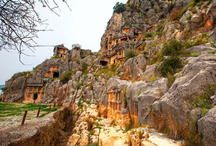 Look up at a series of intricate tombs built into the side of a mountain by the Lycians in Fethiye, Turkey.