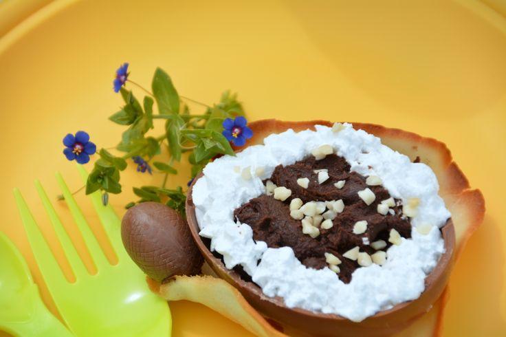 metà uovo di cioccolato, con ganache, ciuffi di panna e granella di nocciola, su cestino di cialda handmade.