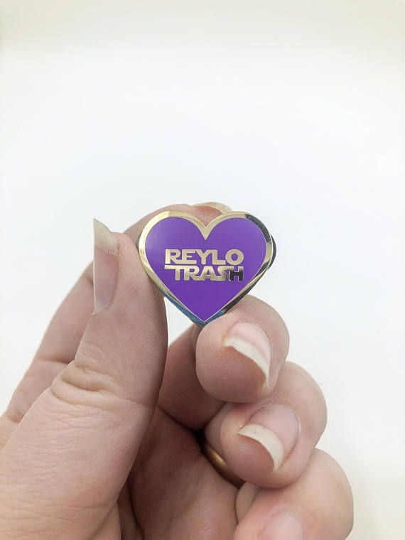 Share the love of your favorite Star Wars ship of Kylo Ren and Rey with this Star Wars Inspired Reylo Trash pin. Pin is a purple heart with a gold border and gold lettering saying Reylo Trash in the heart. The purple and gold signify the coming together of Rey (blue lightsaber)