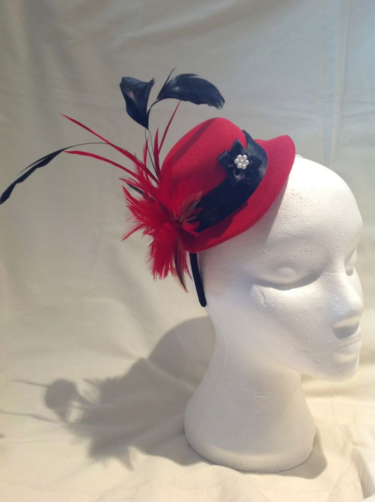 The Lucie is a small fascinator with a red top hat on a black head band the top hat is decorated with a black band and pearl flower matching black and red feathers are included to finish. $70 AUD.