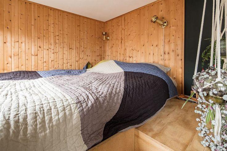 Кровать на антресоли над гардеробом. Стены отделаны лакированной вагонкой, что явно выделяет спальню в гостиной с черными стенами. .