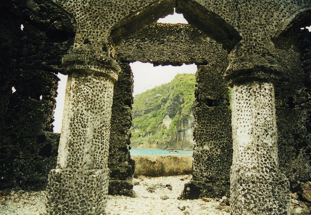 Comoros - The Islands of The Moon   The cliff visible through the arch was the scene of a tragic event in history. The story was told that during an invasion by Slave Traders the woman and children took to the cliffs, where they finally jumped to thei