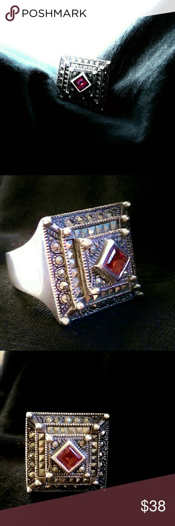 "Marcasite And Garnet Art Deco Ring (Dee Berkley) Show stopping marcasite and garnet ring by famous jewelry designer Dee Berkley. This unique piece has 3 layers of marcasite tiered to a single garnet setting- giving it texture and depth. Band has partial open work, in a zig-zag effect. This is an earlier piece by the artist. Sterling 925 stamp and artist hallmark inside band. Ring has a height of approximately 1/2"" and face measures 3/4"" across. Pictures do not do this beauty justice! This…"