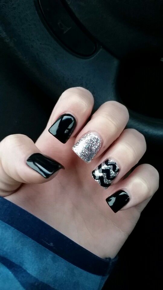 Black shellac gel polish on acrylic fake nails with a sparkly glittery silver accent and another sparkle glitter silver accent with a black chevron design on the ring finger