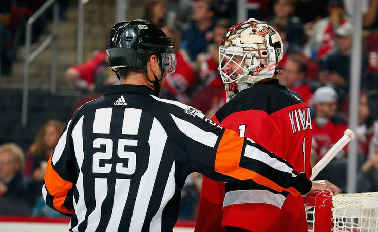 NEWARK, NJ - OCTOBER 20: Referee Marc Joannette #25 talks with Keith Kinkaid #1 of the New Jersey Devils during the game against the San Jose Sharks at Prudential Center on October 20, 2017 in Newark, New Jersey. (Photo by Andy Marlin/NHLI via Getty Images)