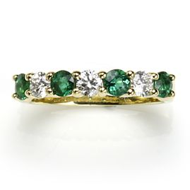 Half eternity ring set with four emeralds (.56 cts) and three diamonds (.41 cts) mounted in 18ct yellow gold. This item has been sold but may be re-ordered. Catalogue No.	101g00558