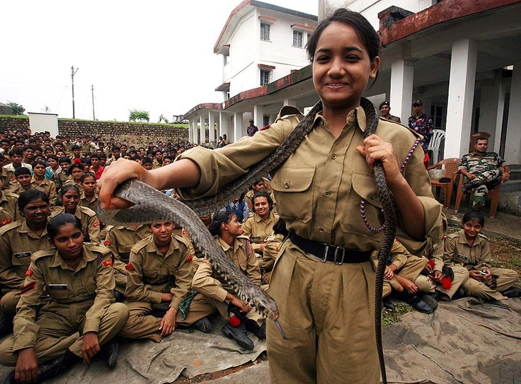 A female recruit from the National Cadet Corps (NCC) handles a snake during a snake conservation and awareness campaign to familiarize a squad of 4 Madhya Pradesh Battalion NCC cadets with the creatures at a training camp in Bhopal, India, on August 9, 2012.