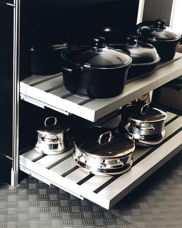 Kitchen storage space featuring sliding shelves for pots and pans