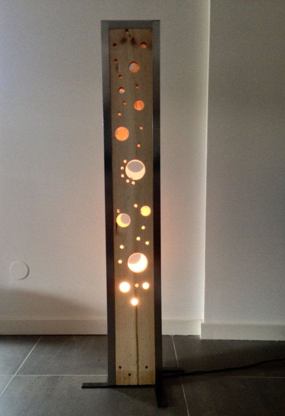 This creation is composed of raw wood and brushed aluminum.  His aesthetic worked makes it pleasant to view both daytime and evening to create mood lighting.  The set is sold with a simple lamp inside  Dimensions: Height: 120 cm - length: 18.5 cm - width: 14.5 cm Weight: 8 kg