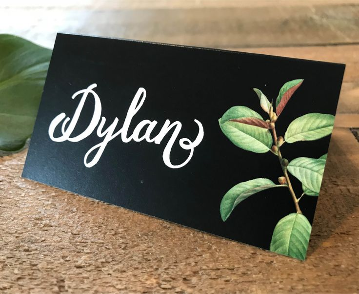 A gorgeous botanic greenery place card | tent card | escort card with a simple leaf and branch graphic on a black background.