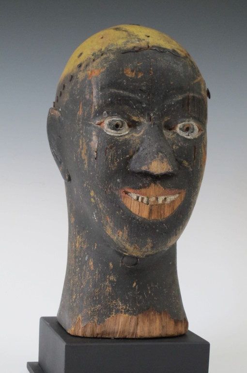 Tonawanda Black Head, U.S.A., 20th century. This carved and painted head was probably made for use in a carnival near Buffalo NY. Related black figures were known to have been made for cranking caliopies. This head may also have seen use in an arcade ball toss.