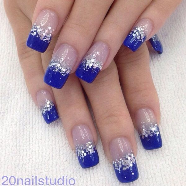 Beautiful dark blue nail art design in French tips. The French tip designs are n blue nail polish and are bordered with silver glitter and sequins as they transition in to clear polish when the design reaches the cuticle of the nails.