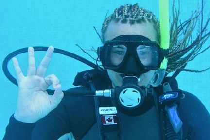 A scuba diver signals that she has finished the mask clearing skill.
