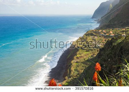 Beautiful romantic view on Madeira Island coastline - high cliffs, small village, rocks, beach, red flowers, turquoise sea water and blue sky on the horizon.