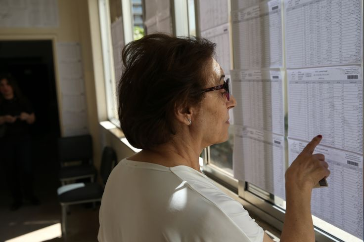 A Lebanese woman looks for her name on a polling list before casting her vote, outside a polling station during the municipal elections in Beirut. (Hussein Malla / AP)