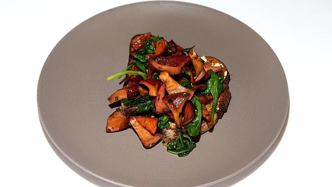 Wild mushrooms and spinach leaves on toast.