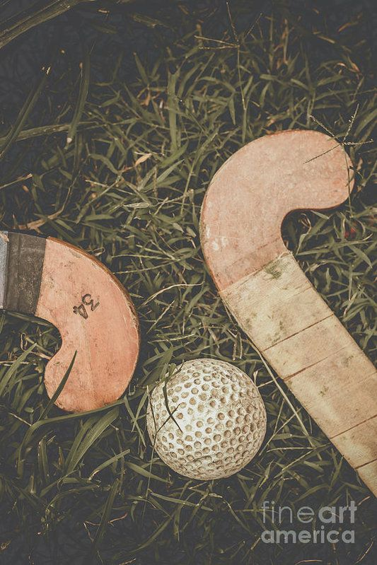 Antique still life photograph on two wooden hockey stick on a grass playing field. Vintage Hockey by Ryan Jorgensen
