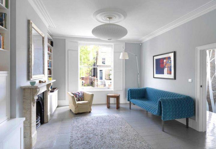 Dettagli architettonici che parlano di un passato vittoriano e borghese, quali il camino in marmo e i decori sul soffitto, sono stati riportati alla luce nel lavoro di ristrutturazione della casa londinese di Ben Kilburn. La sala giocata in grigio comprende l'iconico divano disegnato da Inga Sempé per Ligne Roset