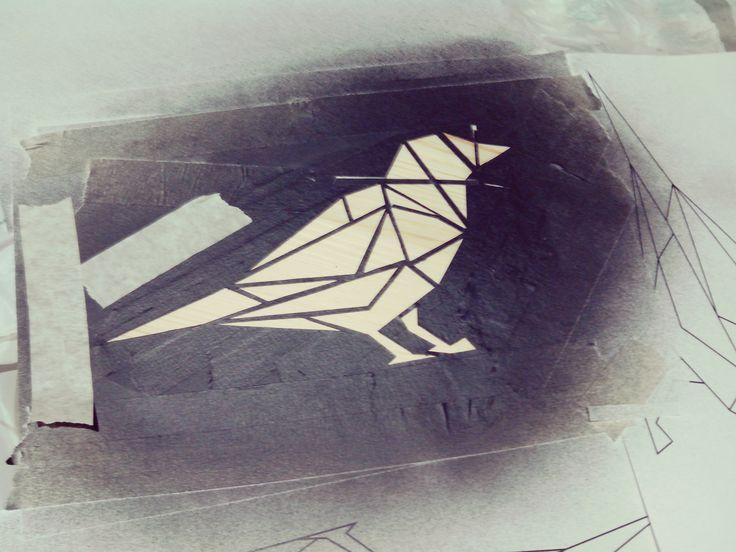 Después de haber recortado todo el diseño del pájaro, se sujeta con cinta a la tapa del taburete y pintamos con el spray negro