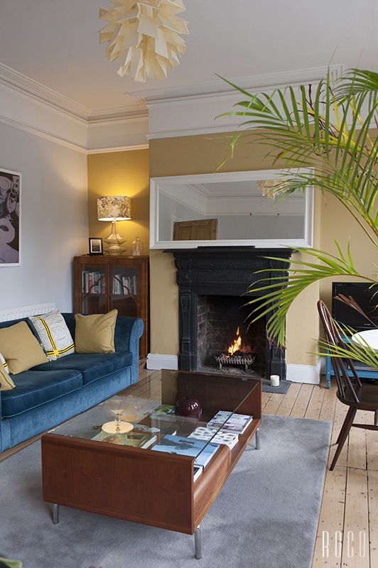 Mustard and white Living Room with fire and blue velvet sofa