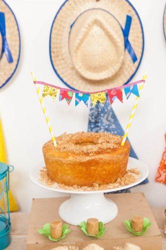 O varal de bandeirinhas fica um charme enfeitando o bolo, que, bem no clima de festa junina, é de fubá, com farofa de paçoca por cima