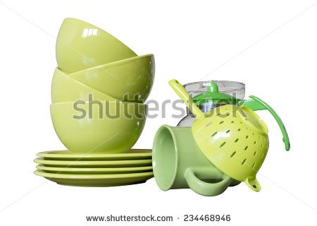 green porcelain dishes with bowls, plates, mug, teapot and tea-strainer isolated on white - stock photo